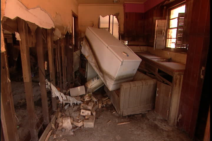 Interior of wrecked kitchen, refrigerator is toppled onto sofa, walls torn apart in New Orleans after Hurricane Katrina.
