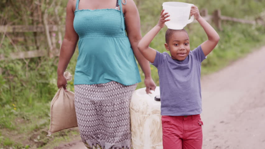 Young African boy and his mother carry containers of water back to their village