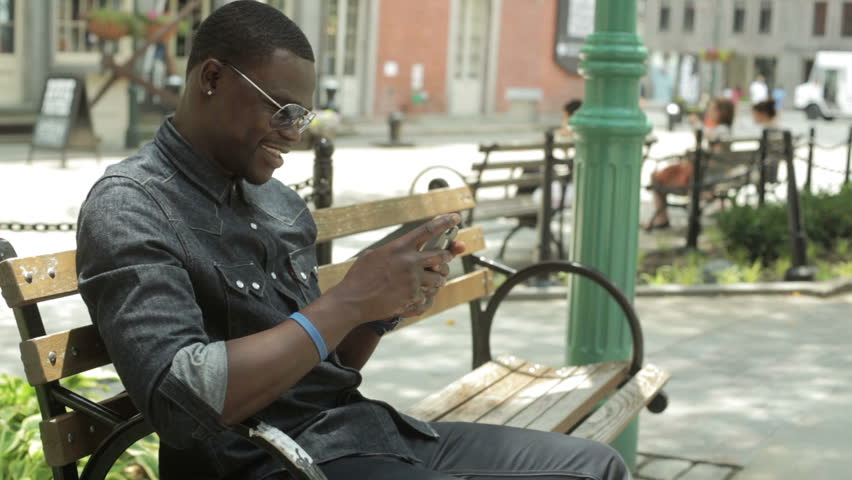 Black guy checking his email on his cell phone