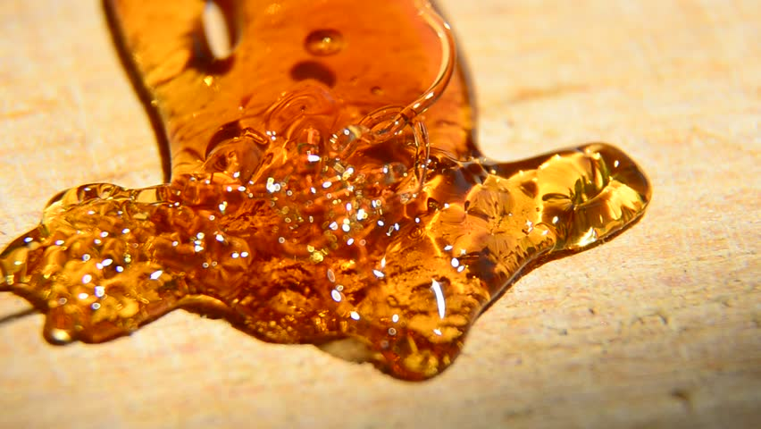 Pouring Golden Organic Honey and forming abstract arrow on wooden surface - HD stock footage clip