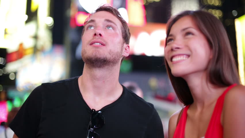 Happy young couple on Times Square, Manhattan, New York City at night. Beautiful young multi-ethnic couple dating smiling having fun on date or as tourists in USA. Asian woman, Caucasian man.