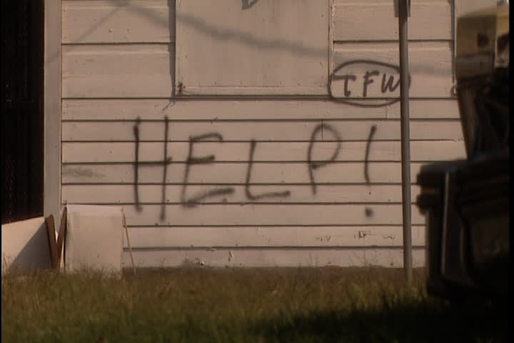 The word help! spray painted on the clapboard side of a house in New Orleans after Hurricane Katrina (October 2005). Traffic passes in foreground.