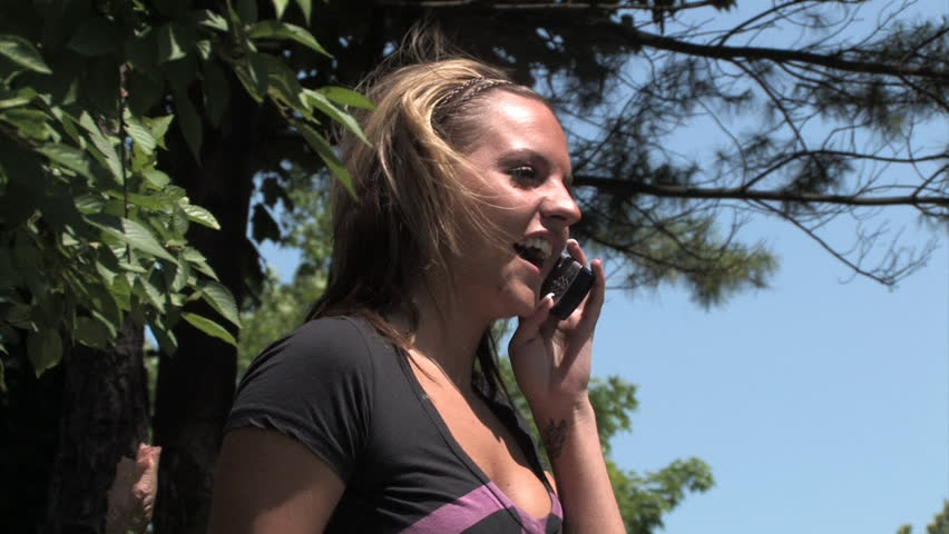 A young woman talks on a cellular phone in the park. - HD stock footage clip