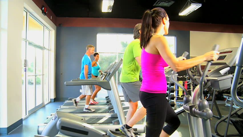 Male female gym members exercising on modern equipment