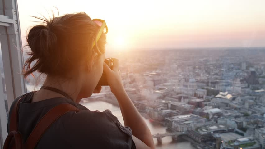 Tourist taking photograph of sunset in london skyline view from The Shard