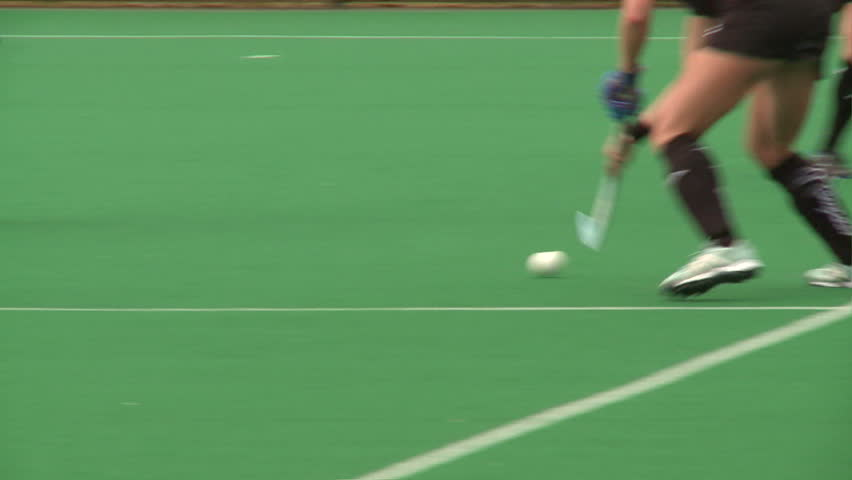 Field Hockey played on astro turf. woman's field hockey played on a rainy day in London.