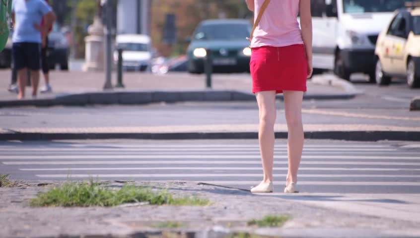 Hot sexy legs of young adult women walking down the street.