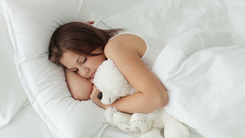 Pretty sleeping girl hugging teddy bear
