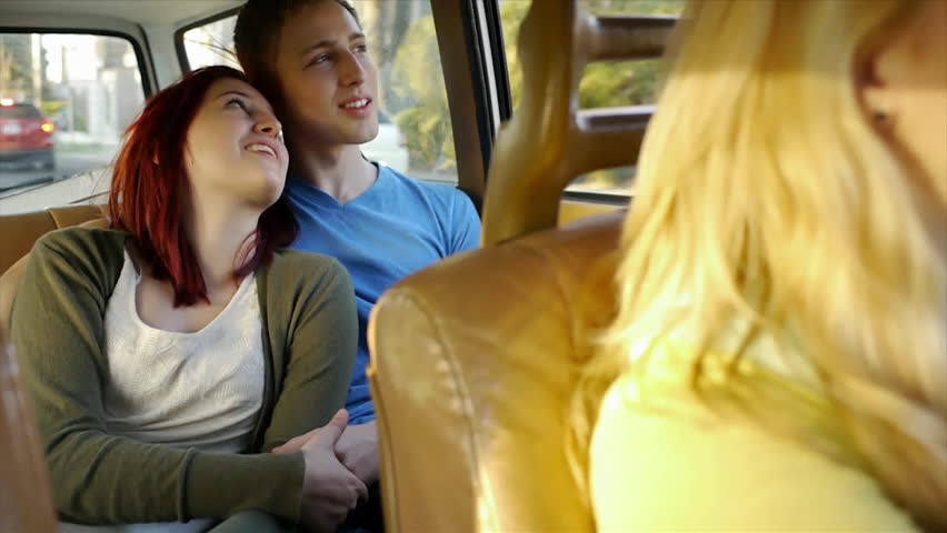 Teen Couple Hold Hands And Talk In The Backseat, While