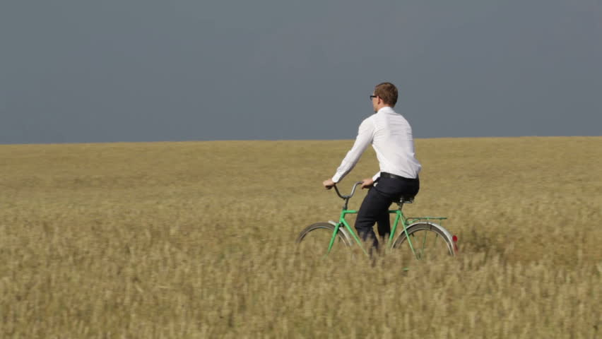 Young entrepreneur riding a bike across the cultivated land, ecology concept