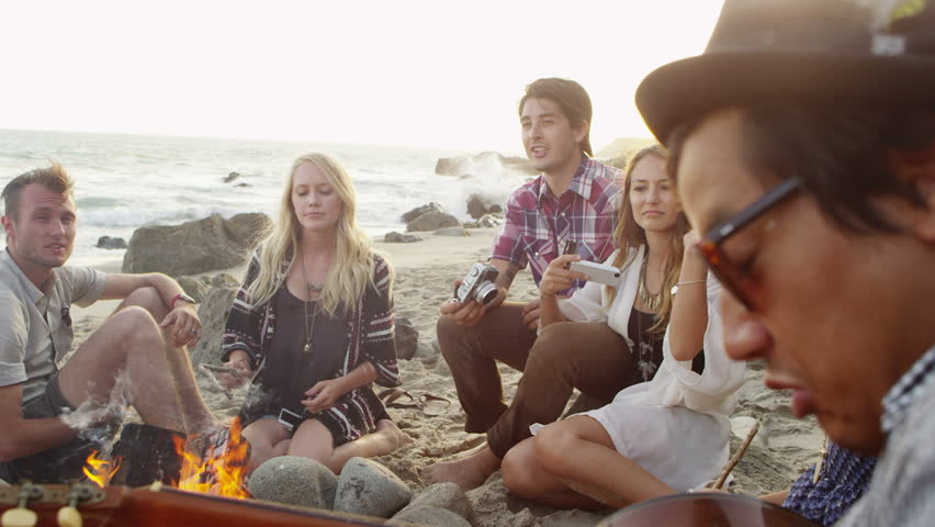 Group of young people hanging out at beach around campfire