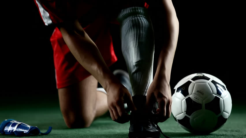 Soccer player puts on shin pads, preparing to play. Close up shot - HD stock footage clip