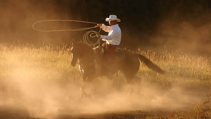 Cowboy roping at sunset, slow motion