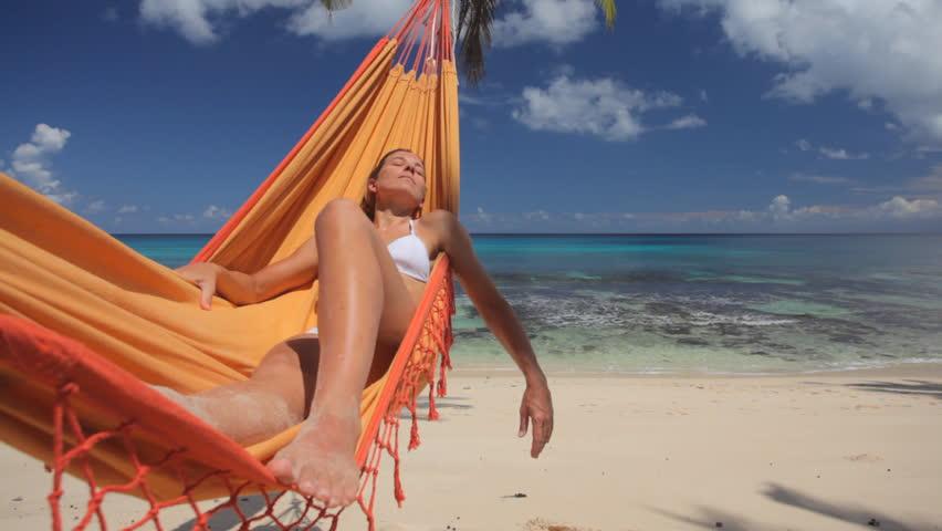 woman in bikini relaxing in hammock on sandy beach, with audio
