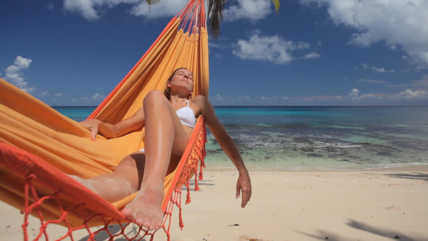 woman in bikini relaxing in hammock on sandy beach, with audio
