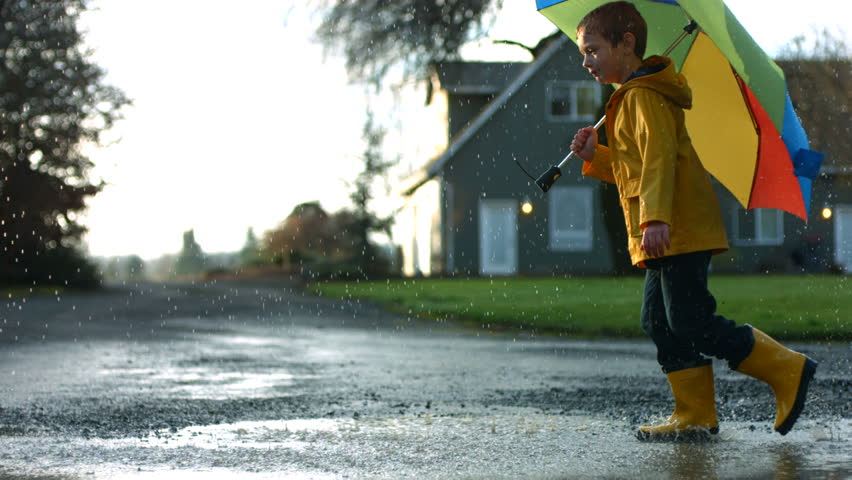 Young boy running through puddles with umbrella, slow motion