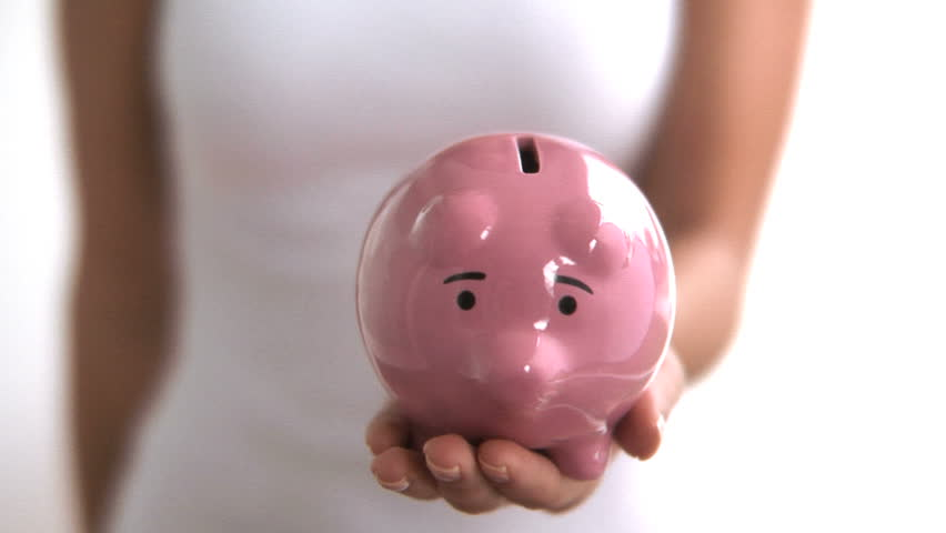 Woman holds up piggy bank against white background