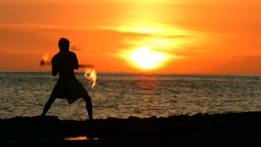 Fire knife dancer performs at sunset
