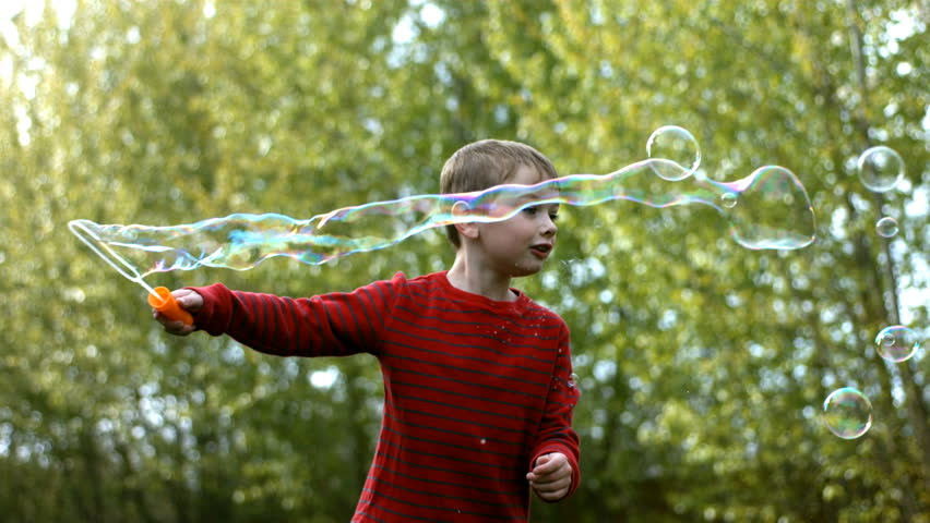 Young boy making bubbles, slow motion