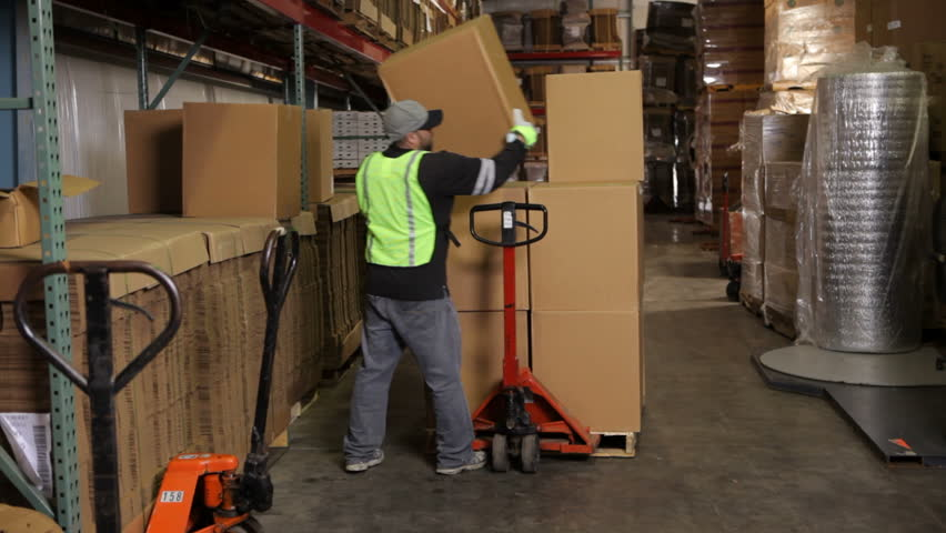 Delivery man moving packages in warehouse