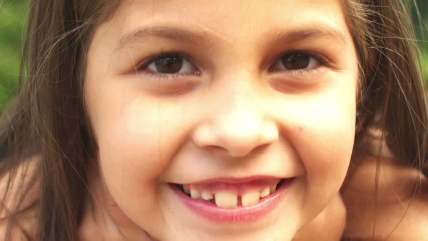 Adorable little girl smiles for the camera. Close up shot.