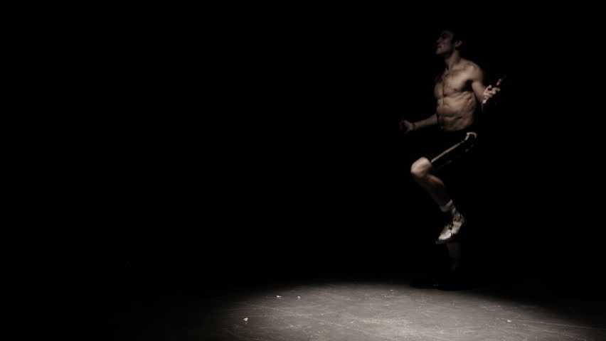 A fighter does some jump rope exercises in a dark room under a light - HD stock video clip