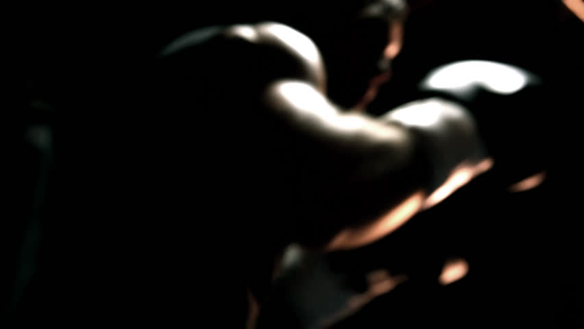 Muscular athlete practices boxing on a punching bag. Close up shot. - HD stock video clip