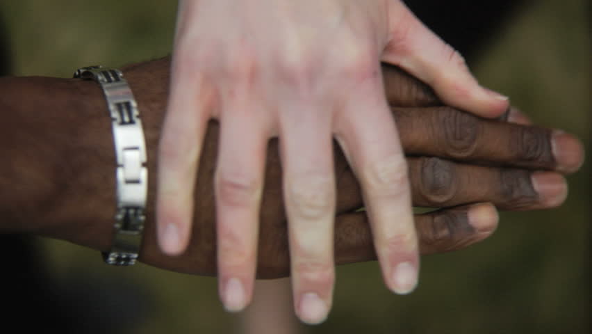 Close up of people putting hands together