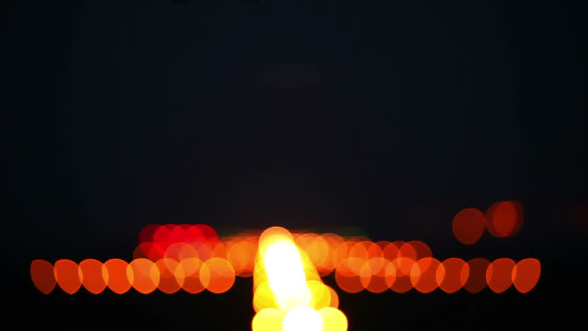 View to the landing lights of the runway at night. Rack focus.