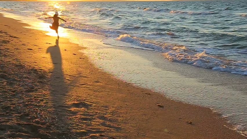 child running along the surf at sunset. Slow motion