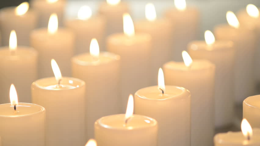 White Candles Burning Peacefully. One Candle In Focus, Other Candles Out Of Focus