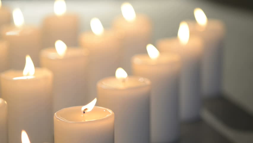 Dolly Shot Of White Candles Burning With Soft Candle Light. Front Candles In Focus, Back Candles Out Of Focus