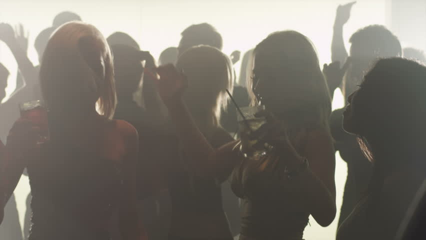 A group of attractive silhouetted young adults dance in a smokey club in slow motion