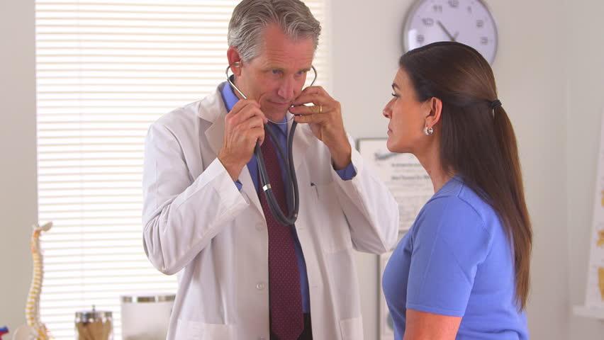 Doctor listening to elderly woman's heartbeat