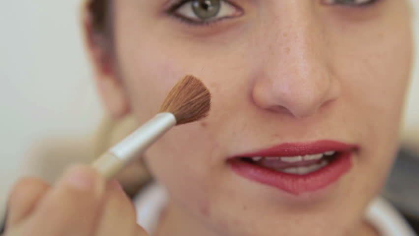tight close up of young millenial teenage girl putting on makeup applying concealer