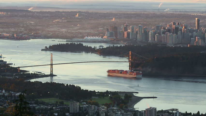 A high angle view of downtown Vancouver, the Lions Gate Bridge, and Burrard Inlet at sunrise. A freighter passes under the bridge as the sun comes up. British Columbia, Canada. - HD stock footage clip