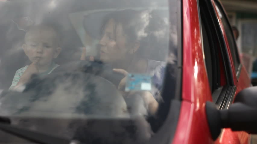 Happy baby and mother in the car say good bye and kiss the finger to farewell