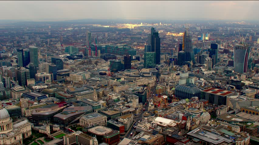 Dramatic aerial shot of the City of London financial district skyline. Features the Gherkin / 30 St Mary Axe building and other famous landmarks.