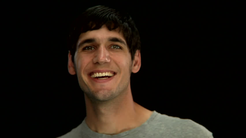 A young man says hello to the camera on a black background