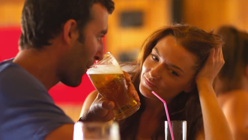 A girl and a boy sit at a bar drinking, talking, laughing and flirting together