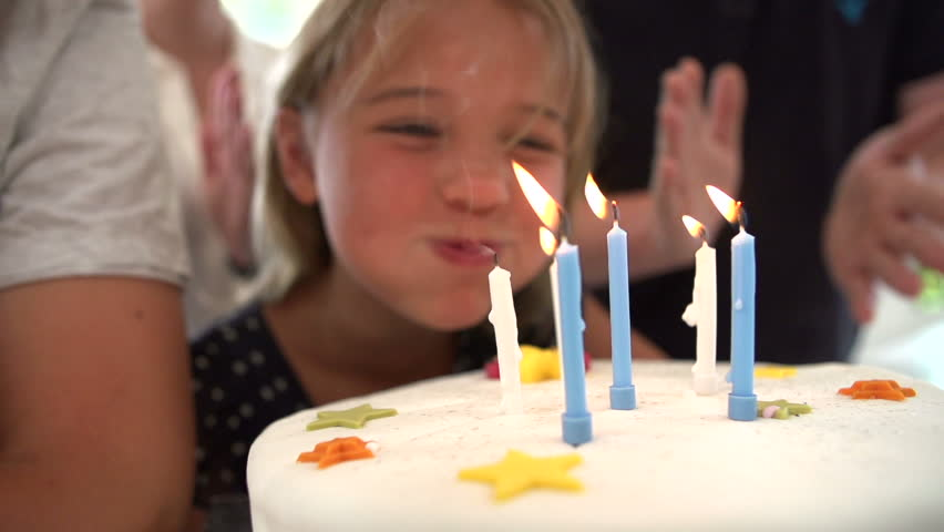 Little girl blows out candles on birthday cake at party, slow motion sequence