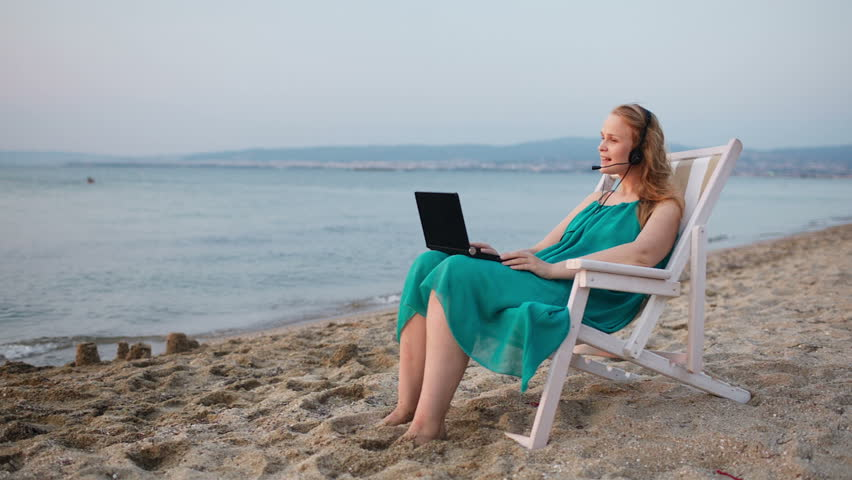Woman relaxing at the beach in a deckchair alongside the ocean with her laptop computer and wearing a headset talking with her friend with skype - HD stock video clip