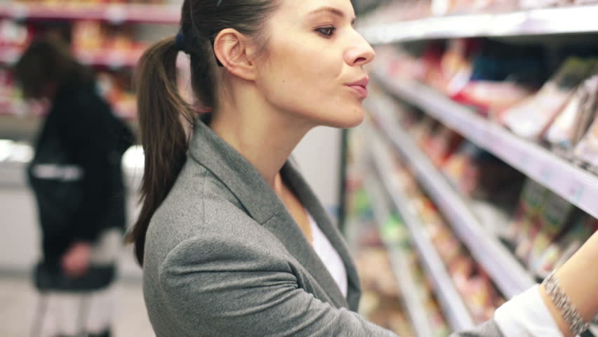 Woman in supermarket choosing ham from the fridge