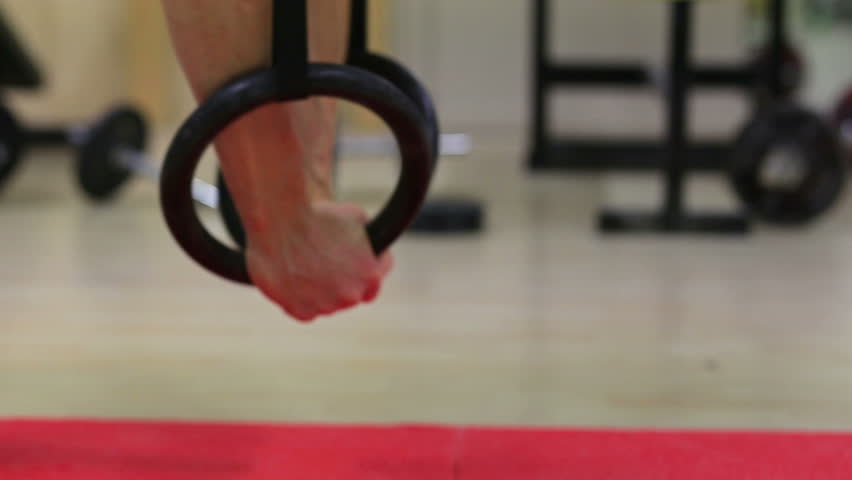 Close up of a climber training indoor with gymnastic rings