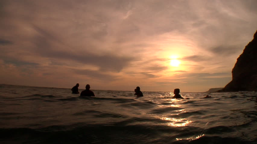 Silhouette shot of five surfers sitting in the ocean as the sun sets behind them.