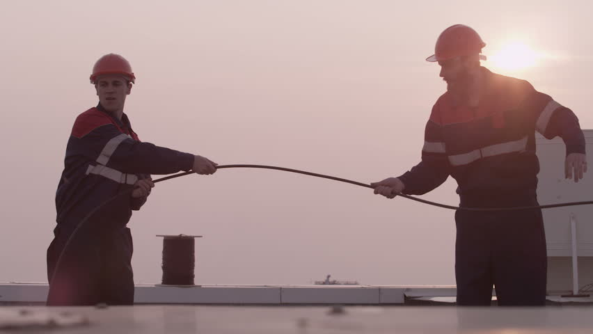 Mans Workers unwinds internet cable on the roof - HD stock video clip
