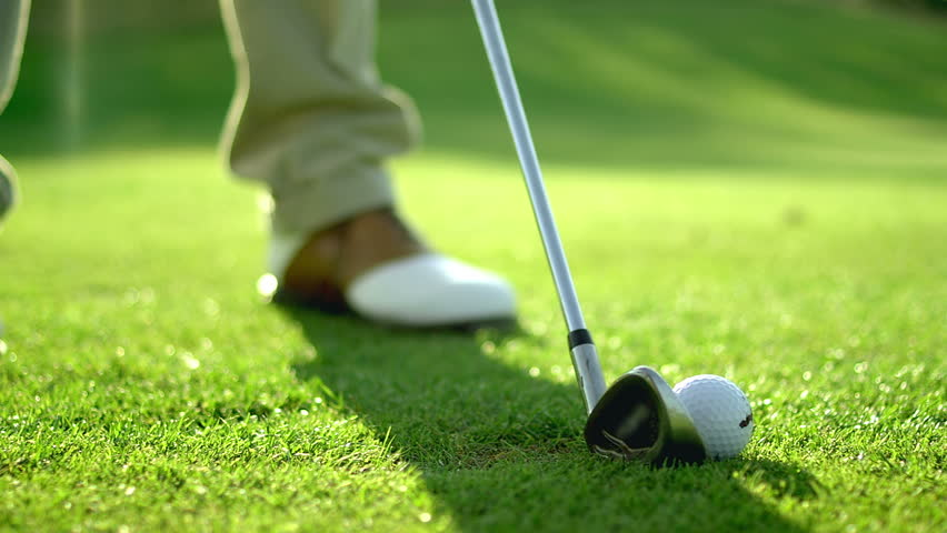 Close up of a golf ball being hit by a club on the grass, in slow motion - HD stock video clip