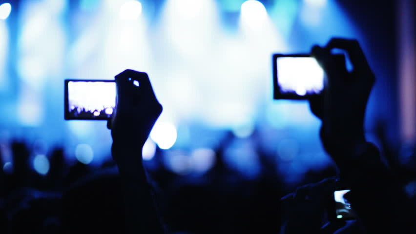 Fans at a concert. Hands hold cameras with digital displays among people at rock concert.