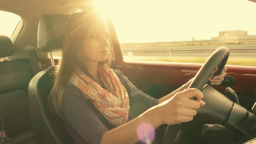 brunette girl driving a car, gorgeous sun flare and grading. Occasional exposure variations are caused by the road signs blinding the sun for a second