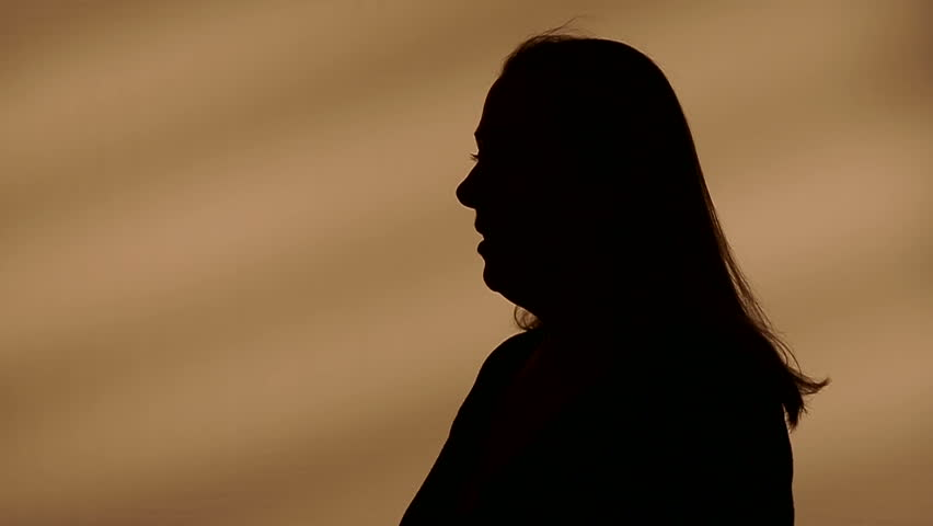 Female silhouette goes with her hands through her hair
